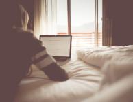 Frau liest Blog im Bett